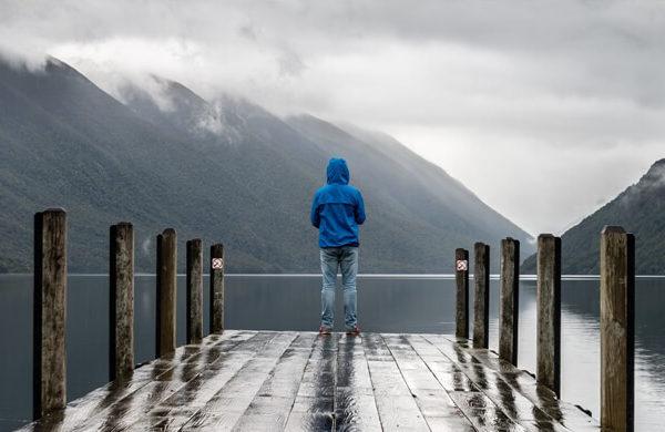 Person auf Steg vor wolkenverhangenen Bergen